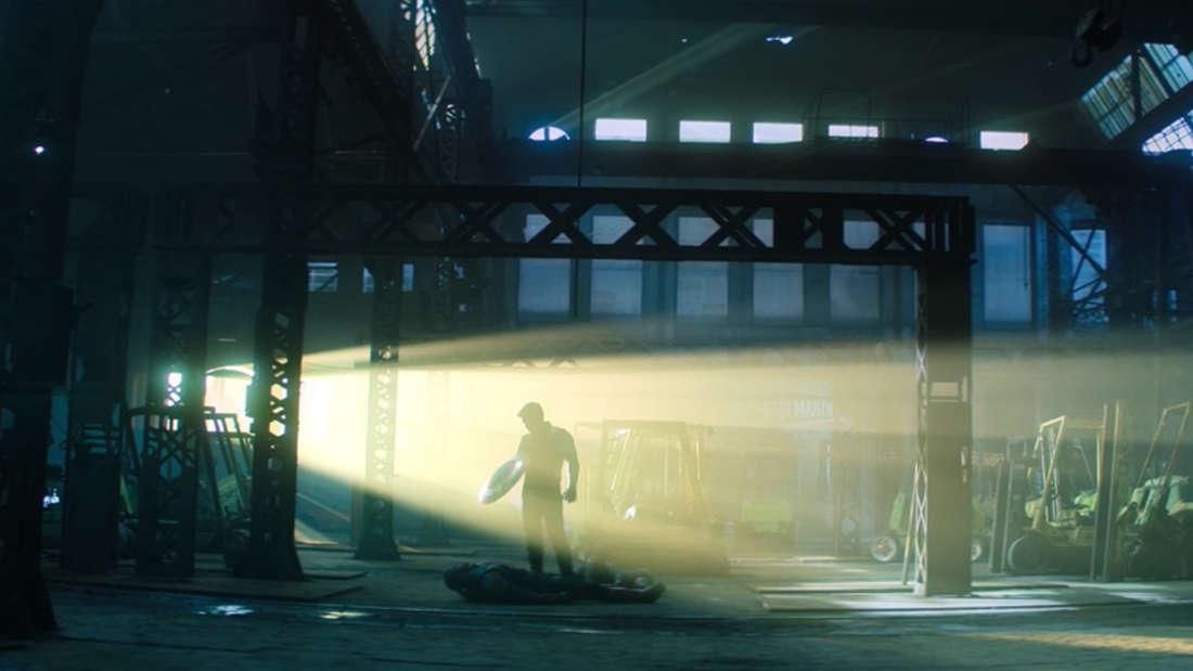 """Bucky Barnes, der in der neuesten Folge von """"The Falcon and The Winter Soldier"""" mit dem Schild von Captain America über einem ausgeknockten Captain America steht, während er von einem Licht angestrahlt wird."""