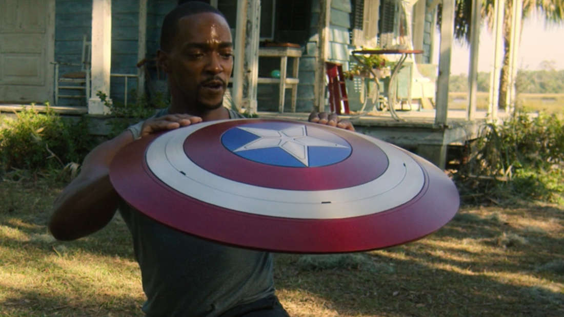"""Sam Wilson hält den Schild von Captain America in """"The Falcon and The Winter Soldier"""" in den Händen und sieht stolz aus."""