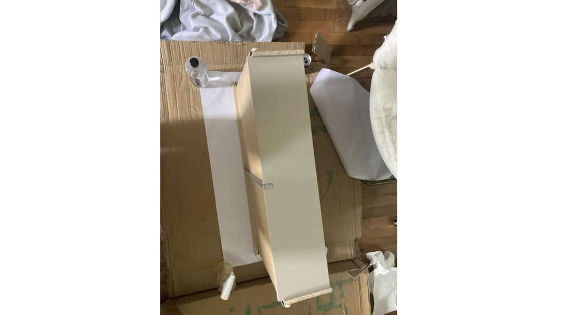 Eine Schublade, auf die eine Tapete geklebt wird