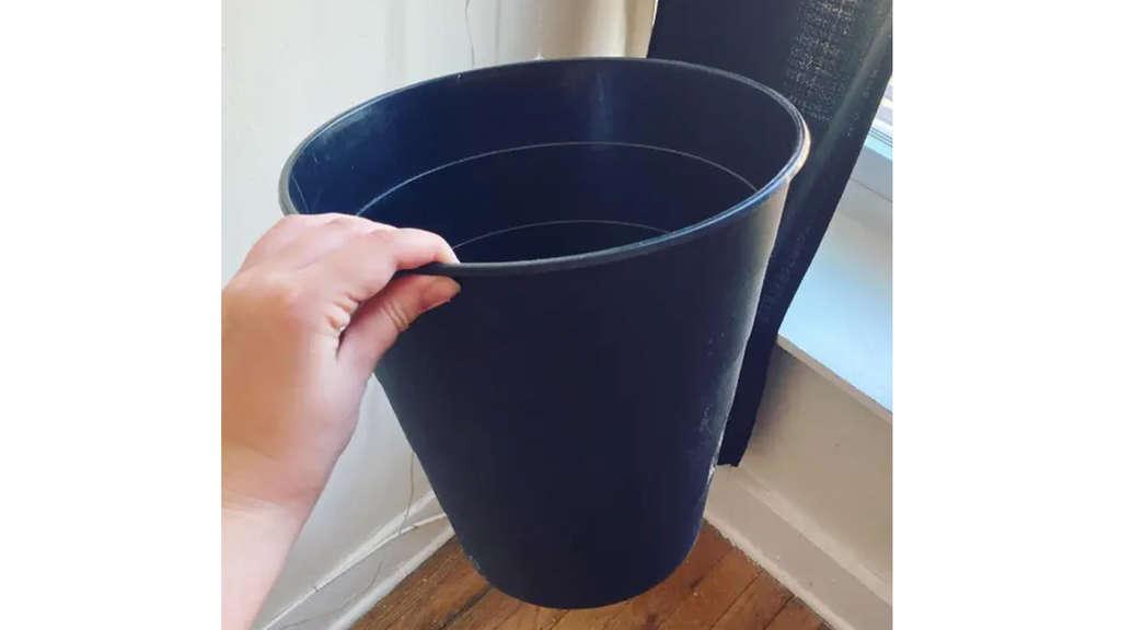 Ein schwarzer Mülleimer von Ikea, den Natasha festhält.