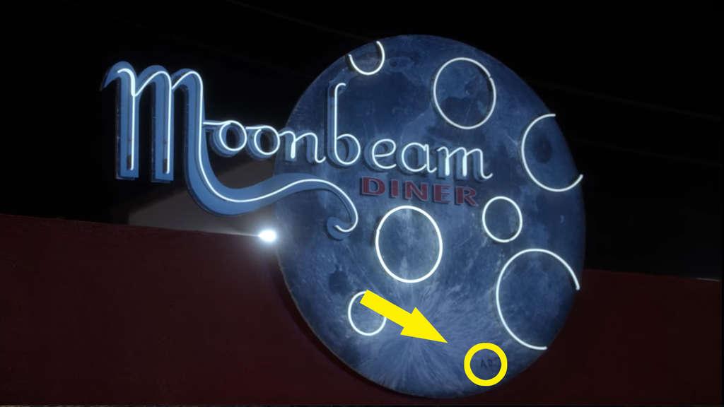 Ein Diner-Schild, mit dem Namen Moonbeam. Das Schild hat die Form des Mondes und unten ist darauf A.D. geschrieben worden.