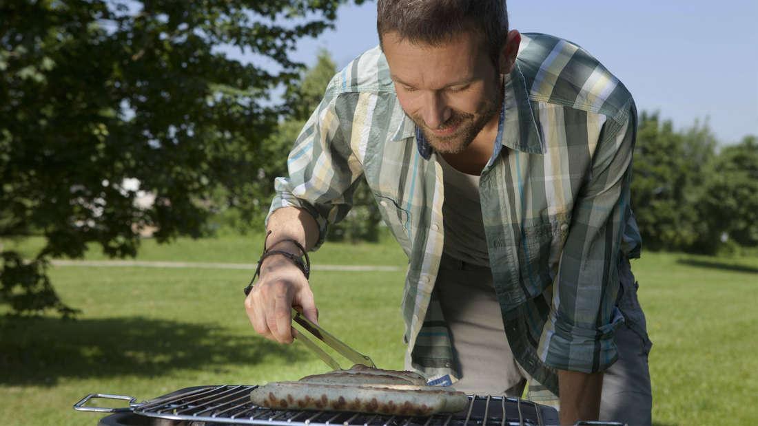 Ein Mann, der draußen Bratwürstchen auf einem Grill grillt.