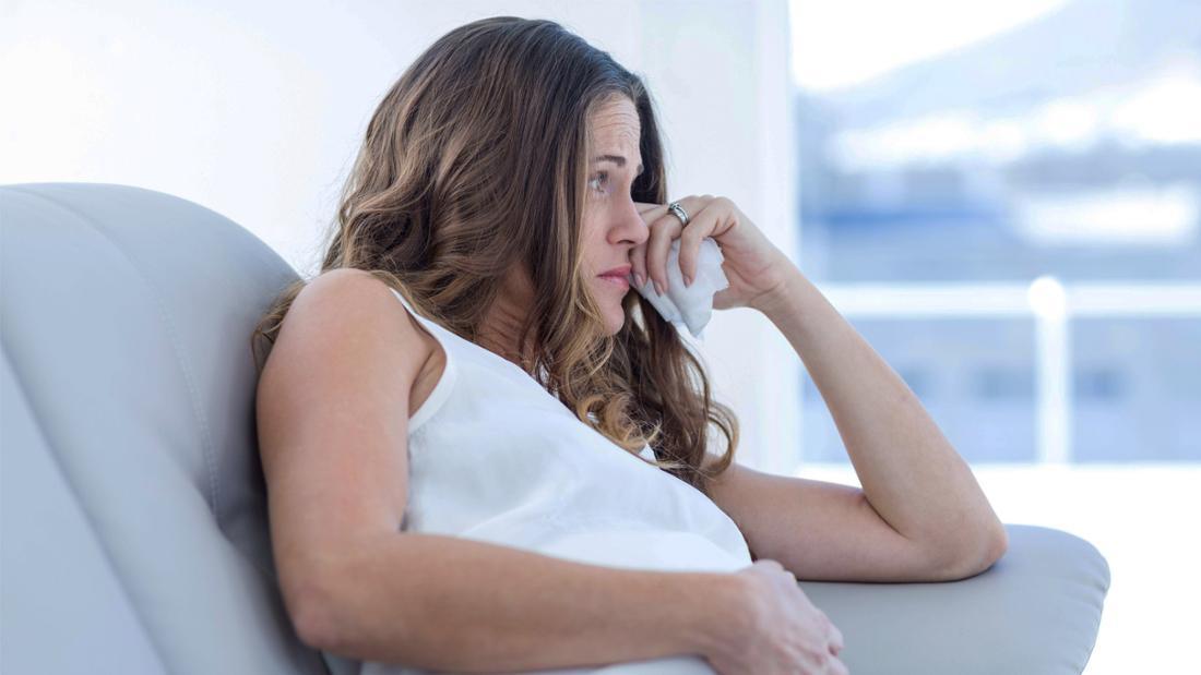 Eine schwangere Frau, die traurig aussieht und ein Taschentuch in der Hand hält.