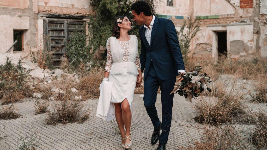Eine Braut und ihr Bräutigam, die gemeinsam vor einem alten Gebäude stehen.