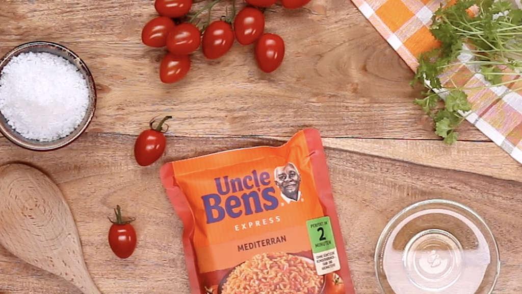 Ein Beutel Uncle Ben's Reis, Tomaten, Zitrone, Gewürze und ein Kochlöffel liegen auf einem Tisch.