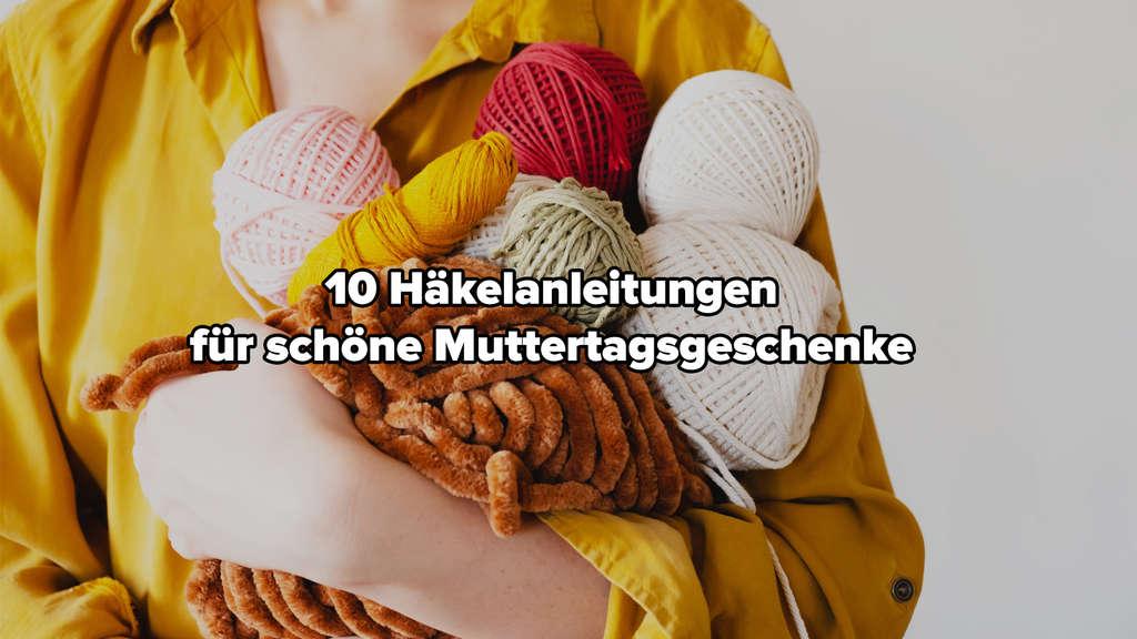 Eine Frau, die mehrere Knäule Wolle hält.
