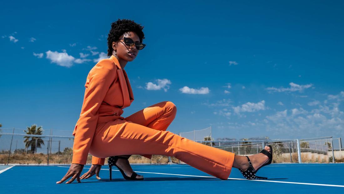 Eine Schwarze Frau in einem orangefarbenen Anzug, schwarzen High-Heels und einer Sonnenbrille auf einem Feld vor einem blauen Himmel mit wenigen Wolken.
