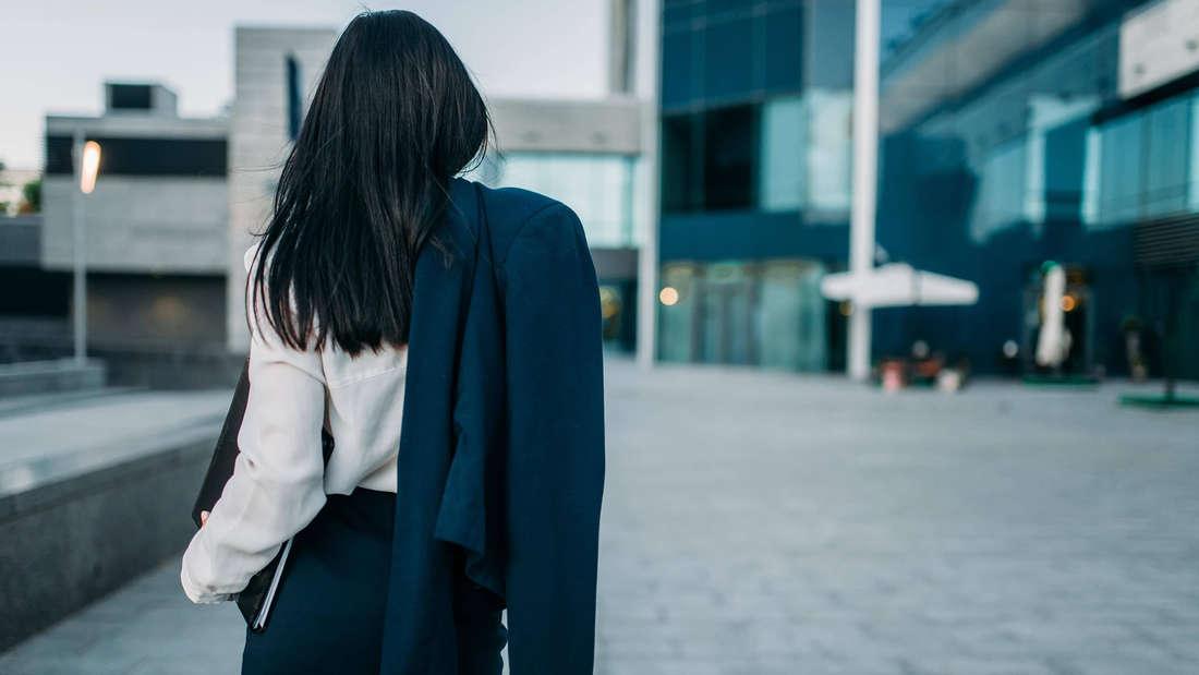 Eine Frau, die einen Anzug trägt und die Jacke davon in der Hand hält. Sie hat der Kamera den Rücken zugedreht.