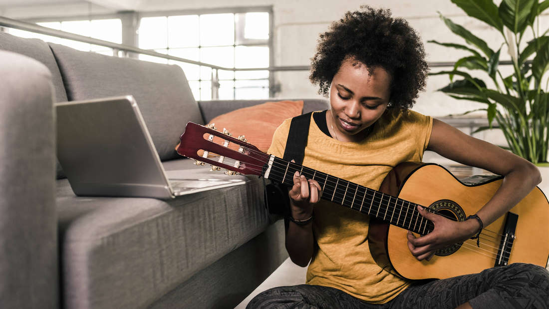 Eine junge Schwarze Frau, die auf dem Boden sitzt und eine Gitarre in der Hand hält und einen Laptop vor sich auf dem Sofa stehen hat.