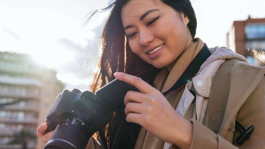 Eine junge Frau, die eine Kamera in der Hand hält und auf diese guckt.