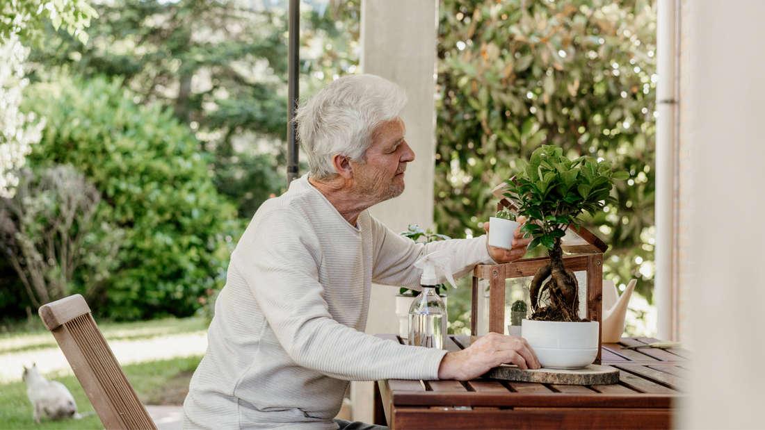 Ein älterer Mann, der sich auf einer Terrasse um Pflanzen kümmert.