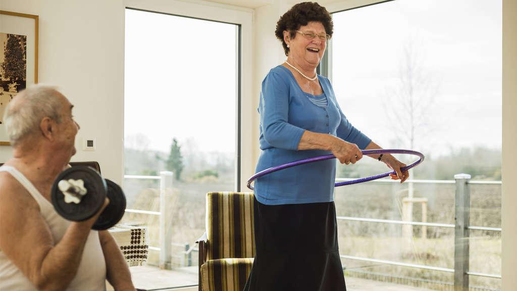Ein älterer Mann, der Gewichte hebt und eine ältere Frau, die Hula Hoop macht