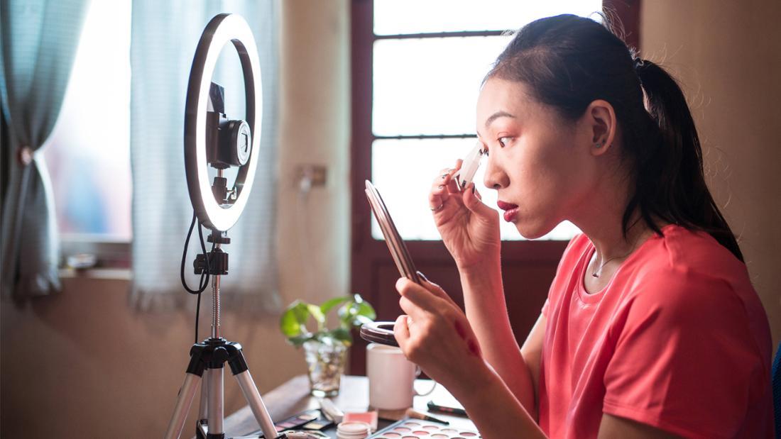 Eine junge Frau, die mit einer Kamera aufnimmt, wie sie sich schminkt.