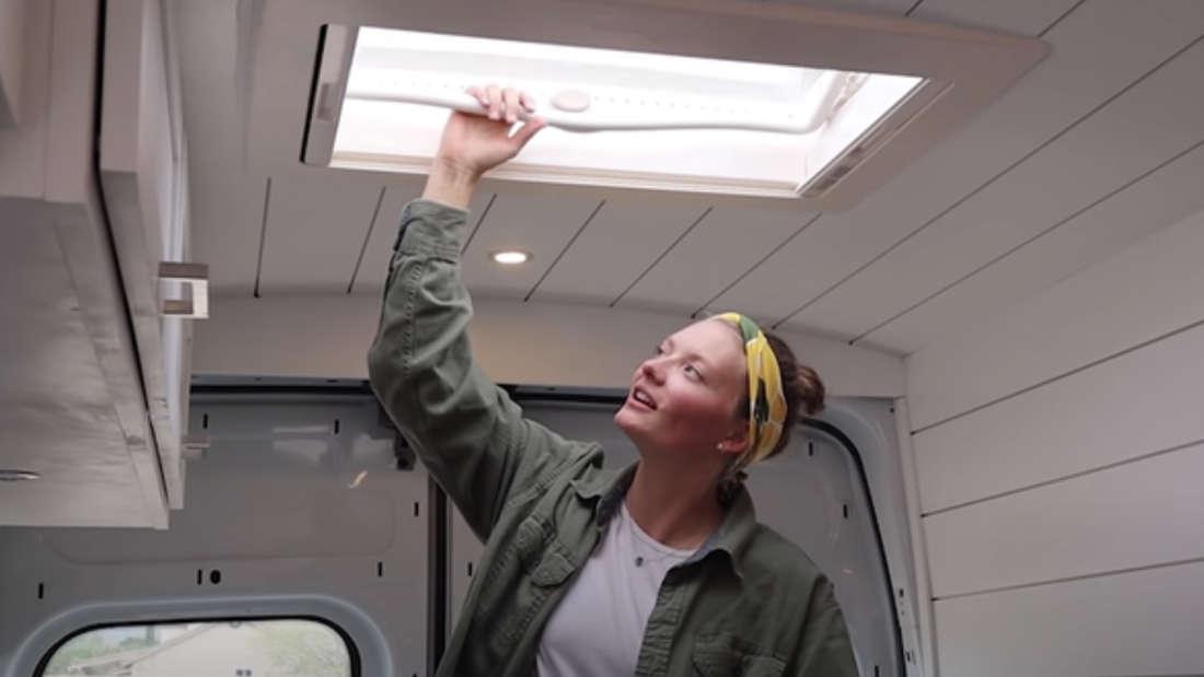 Eine Frau, die in einem Van ein Schiebedach öffnet.