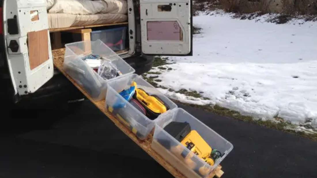 Ein Brett, was aus einem Van herausgerollt werden kann und auf dem Boxen stehen, in denen Sachen verstaut sind.
