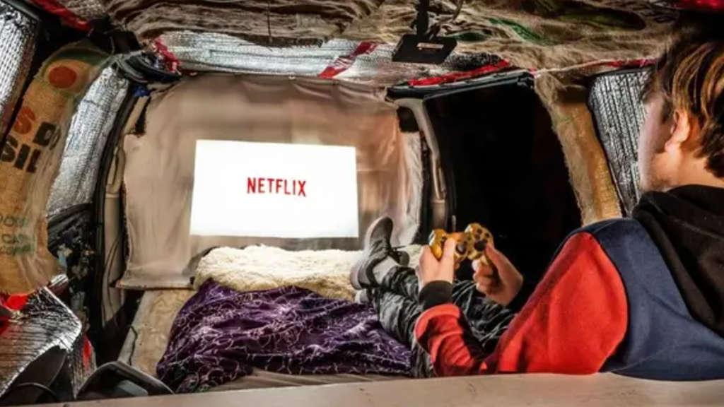 Ein Mann, der in seinem Van sitzt und einen Controller in der Hand hält. Er schaut auf eine Leinwand, die durch einen Projektor Netflix abspielt.