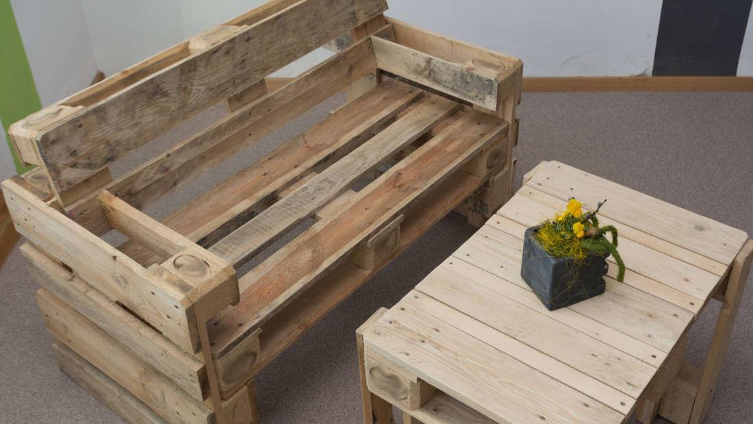 Ein Sofa und ein Tisch, die bei einem Upcycling-Projekt beide aus alten Paletten gebaut wurden. Auf dem Tisch steht eine Pflanze.