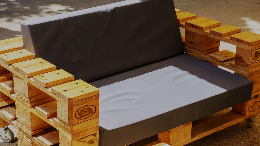 Eine Palette, unter der für ein Upcycling-Projekt Rollen angebracht wurden und die in eine Bank umfunktioniert wurde. Auf ihr sind eine Polster-Sitzfläche und eine Polster-Rückenlehne.