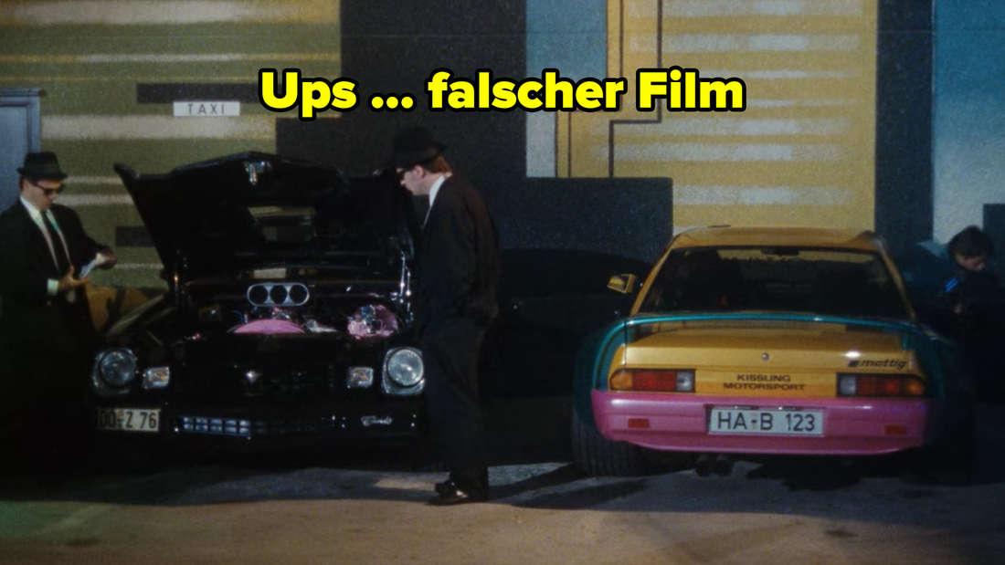 Die Blues Brothers stehen neben einem Auto auf dem Disco-Parkplatz.