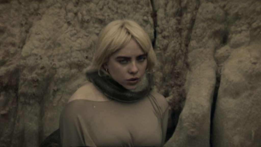 """Billie Eilish im Musikvideo zu ihrer Single """"Your Power"""". Sie blickt in die Kamera, während sich eine Schlange um sie wickelt."""