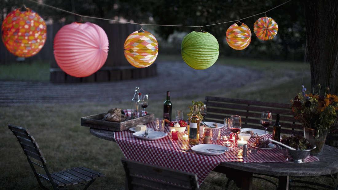 Ein Tisch, über den Lampions hängen und auf dem Essen, Trinken und Geschirr zu sehen ist.