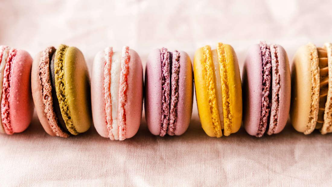 Gelbe, pinke und rosafarbene Macarons auf einem rosafarbenen Tuch.