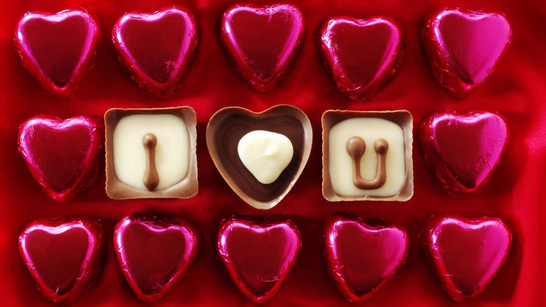 Herz-Pralinen, in deren Mitte drei Pralinen I love you schreiben.