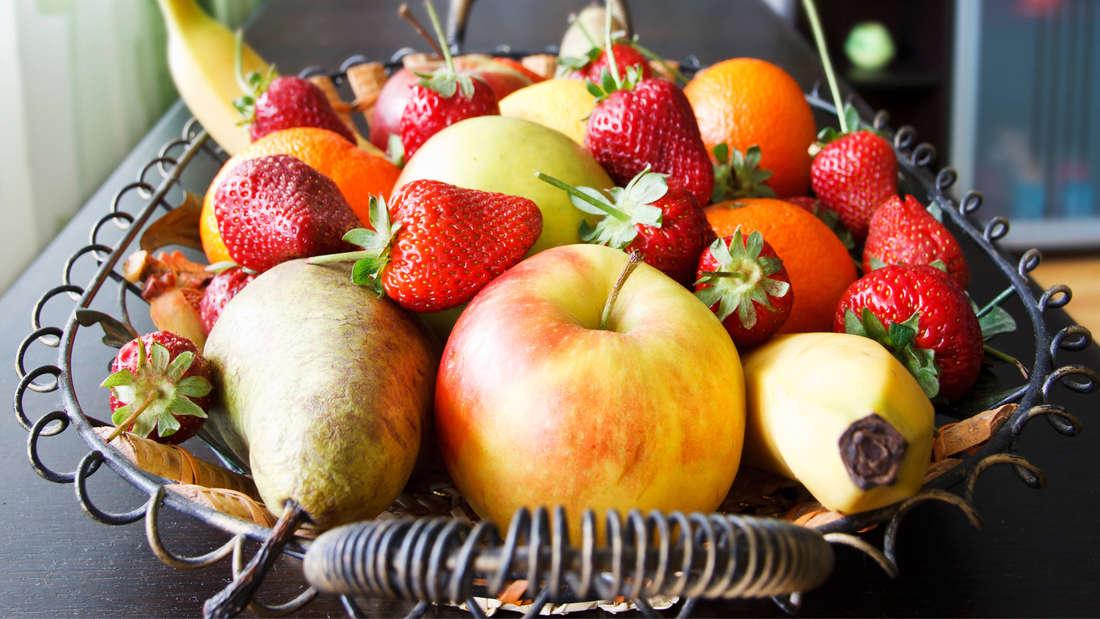 Ein Obstkorb mit Äpfeln, Birnen, Erdbeeren und Bananen.