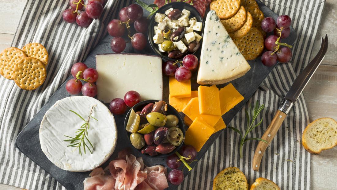 Ein Charcuterie-Board mit Käse, Weintrauben, Cracker und Schinken.