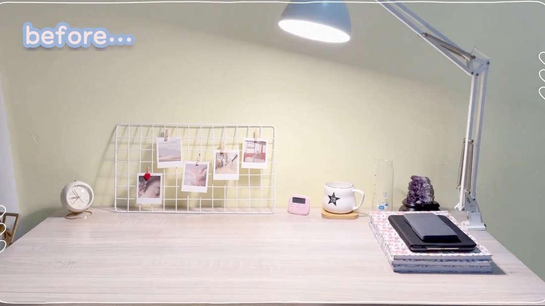 Ein Schreibtisch, auf dem Notizhefte, ein Handy, eine Tasse, ein Untersetzer, ein Wecker und eine Pinnwand mit Fotos stehen. Außerdem scheint eine Lampe auf die Fläche.