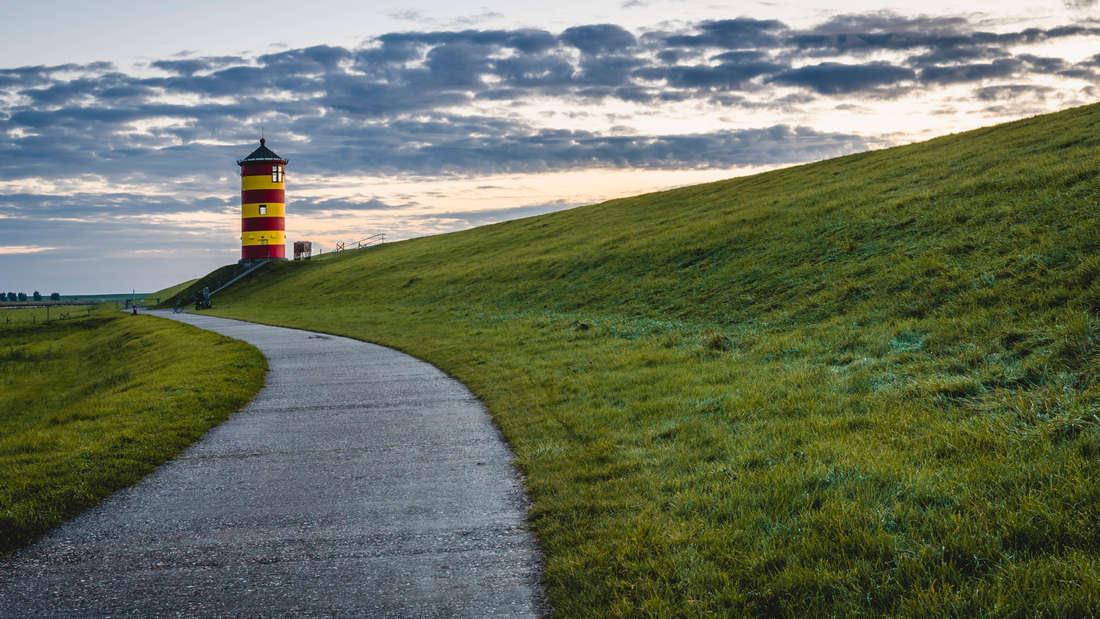 Ein Fußweg, der zum Pilsumer Leuchtturm in Krummhorn führt. Der Leuchtturm ist gelb und rot gestreift.