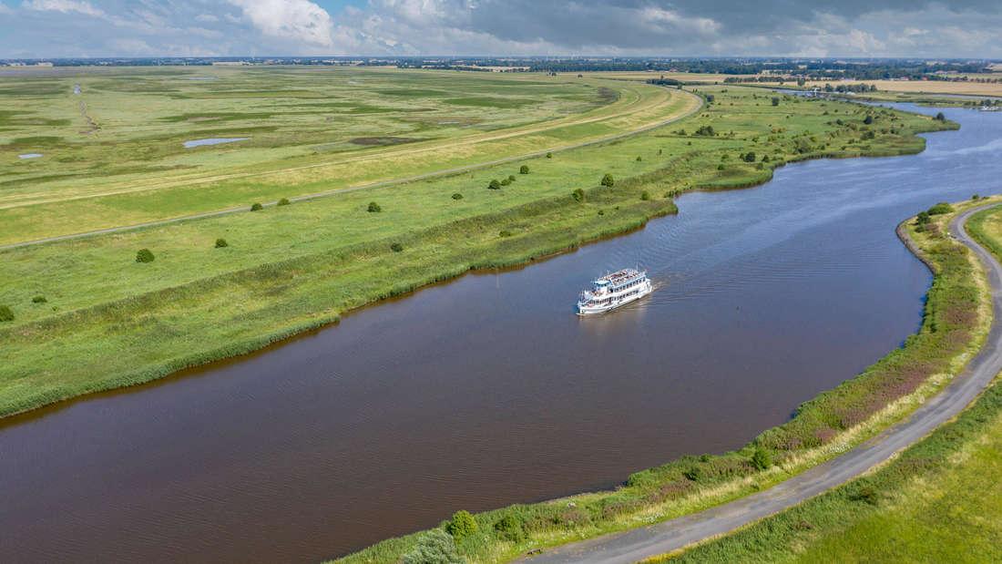 Leyhörner-Sieltief mit großem Fluss, der von Grün umrandet wird. In der Mitte des Flusses befindet sich ein Schiff.