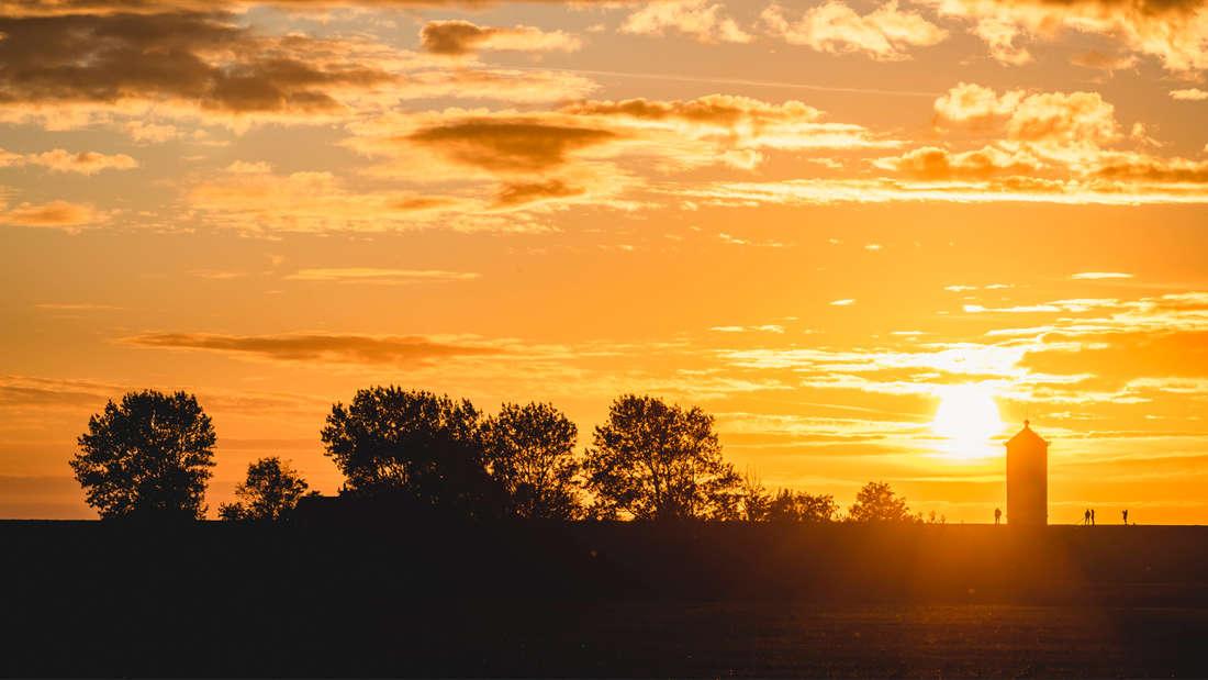 Die Silhouette des Krummhorner Leuchtturms, der von der untergehenden Sonne angestrahlt wird. Es sind außerdem viele Bäume und ein paar Wolken zu sehen.