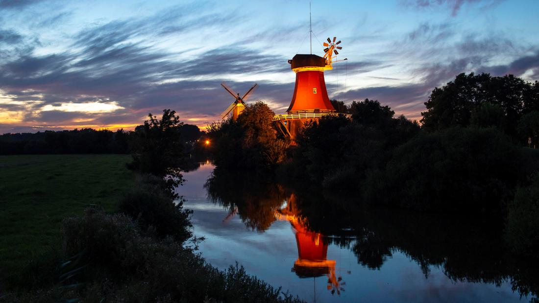 Die Greetsieler Zwillingsmühlen in Ostfriesland, die im Dunklen beleuchtet werden. Sie sind in der Ferne zu sehen, vor ihnen läuft ein Fluss entlang. Der Himmel ist blau und orange.