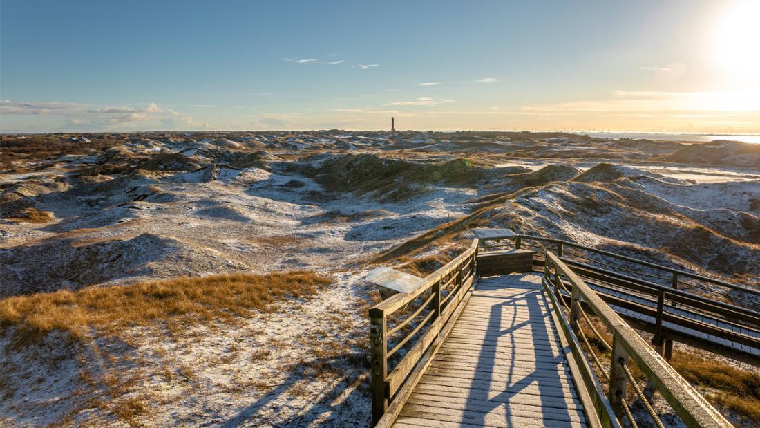 Eine Brücke und eine verschneite Landschaft auf der ostfriesischen Insel Norderney. In der Ferne ist ein Leuchtturm zu sehen.