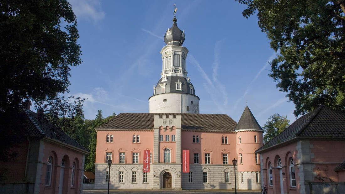 Schloss zu Jever, Ostfriesland von außen mit klarem Himmel und Bäumen. Das Schloss ist in weißen und rosafarbenen Tönen gehalten.