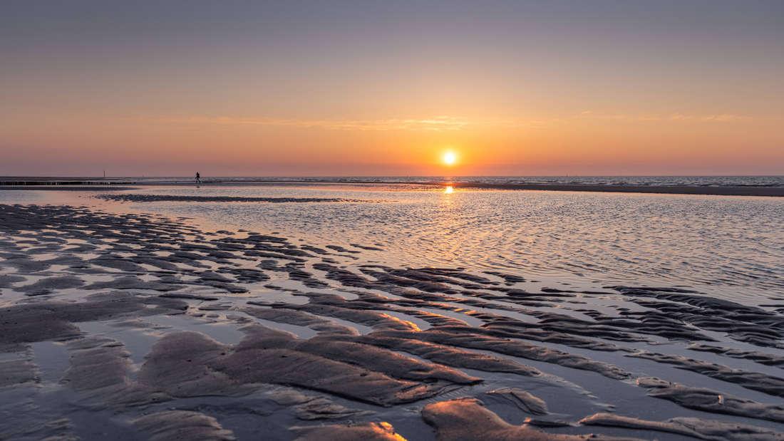 Ein Sonnenuntergang, der vom Wattenmeer vor Norderney angesehen wird. Das Watt und das Wasser, dass sich durch die Einkerbungen bewegt, sind zu sehen. Das Wasser kommt oder geht gerade.