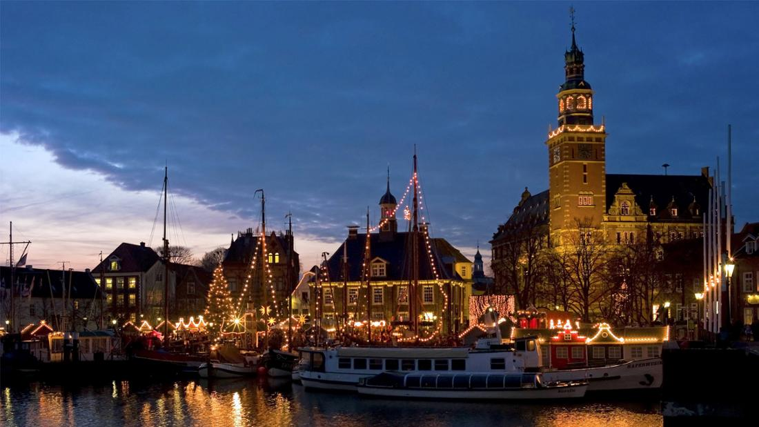 Weihnachtsmarkt mit beleuchteten Schiffen am Hafen in Leer. An den Schiffsmasten sind Lichterketten zu sehen. Im Hintergrund steht außerdem ein großes Gebäude mit Spitze.