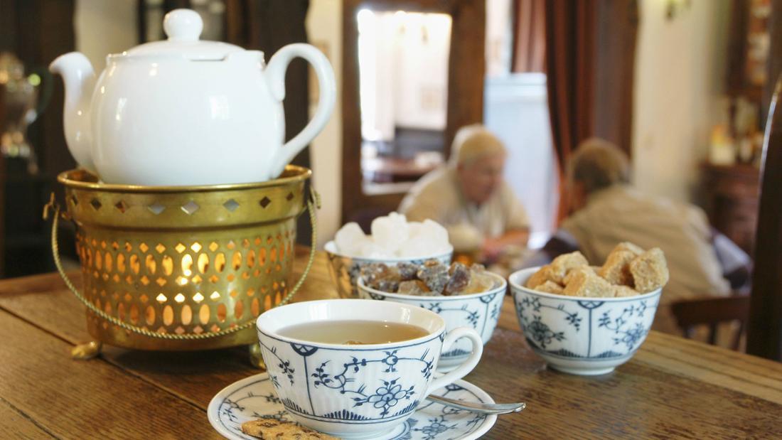 Ostfriesische Teestube mit Porzellantassen und -teller, einem Stövchen, einer Teekanne und Kandis und Keksen auf einem Tisch.