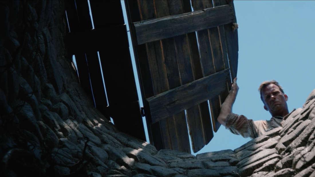 """""""1922"""" auf Netflix: Ein Mann hält die Holzabdeckung eines Brunnens offen und blickt hinein."""