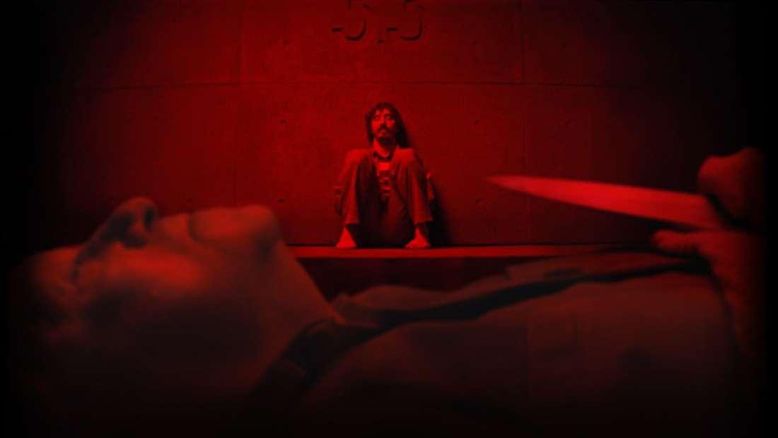 """""""Der Schacht"""" auf Netflix: Das Bild ist komplett in rot getaucht. Ein Mann beobachtet seinen Zellengenossen von der anderen Seite des Raumes beim Schlafen. Der schlafende Mann hält ein Messer."""