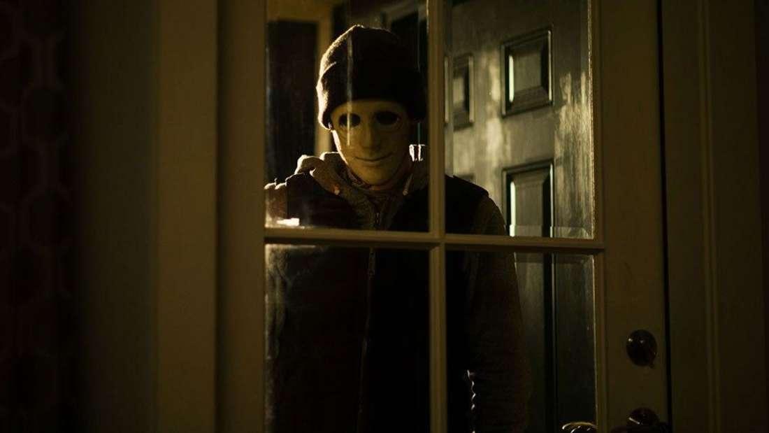 """""""Still"""" auf Netflix: Ein Mann mit Maske steht vor dem geschlossenen Fenster eines Hauses und blickt hinein."""