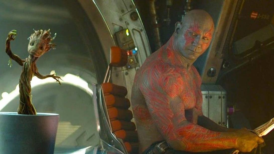 """Drax und Groot aus den """"Guardians of the Galaxy-Filmen"""", die zusammen in einem Raumschiff sitzen. Drax sieht genervt aus, während Groot in einem Blumentopf steht."""