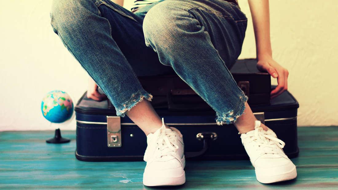 Eine Frau in Jeans, Shirt und weißen Schuhen sitzt auf einem blauen Koffer. Sie ist nur bis zur Hüfte zu sehen. Neben ihr steht ein Globus.