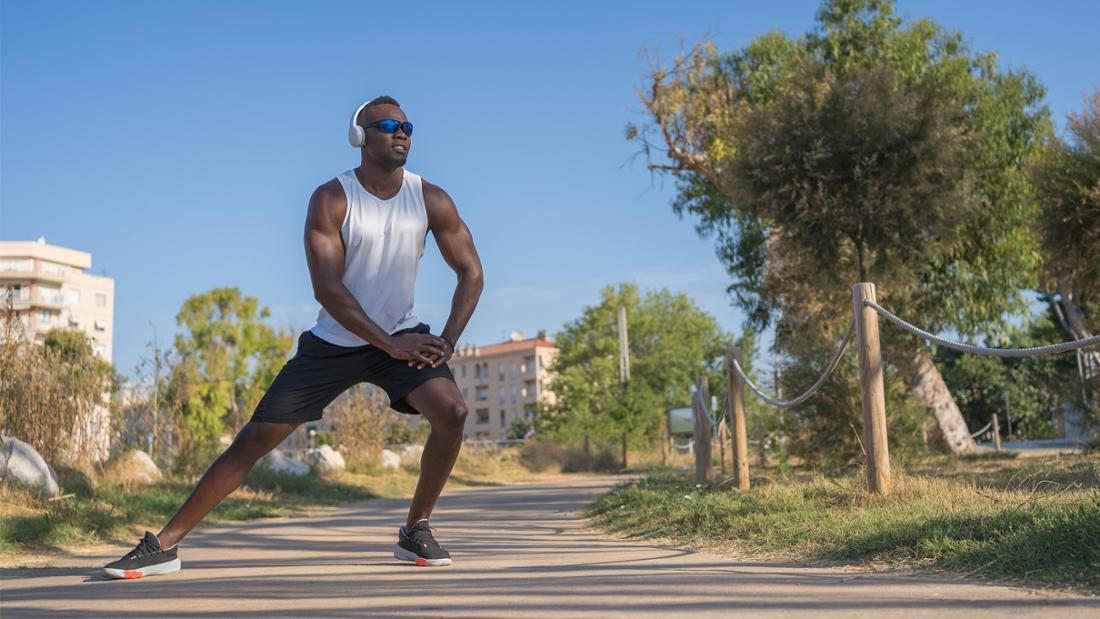 Ein Schwarzer Mann, der auf einer Straße steht und sich streckt. Er ist in Sportklamotten und trägt eine Sonnebrille und weiße Kopfhörer. Seine Umgebung sieht aus wie eine ruhige Gegend in der Stadt.