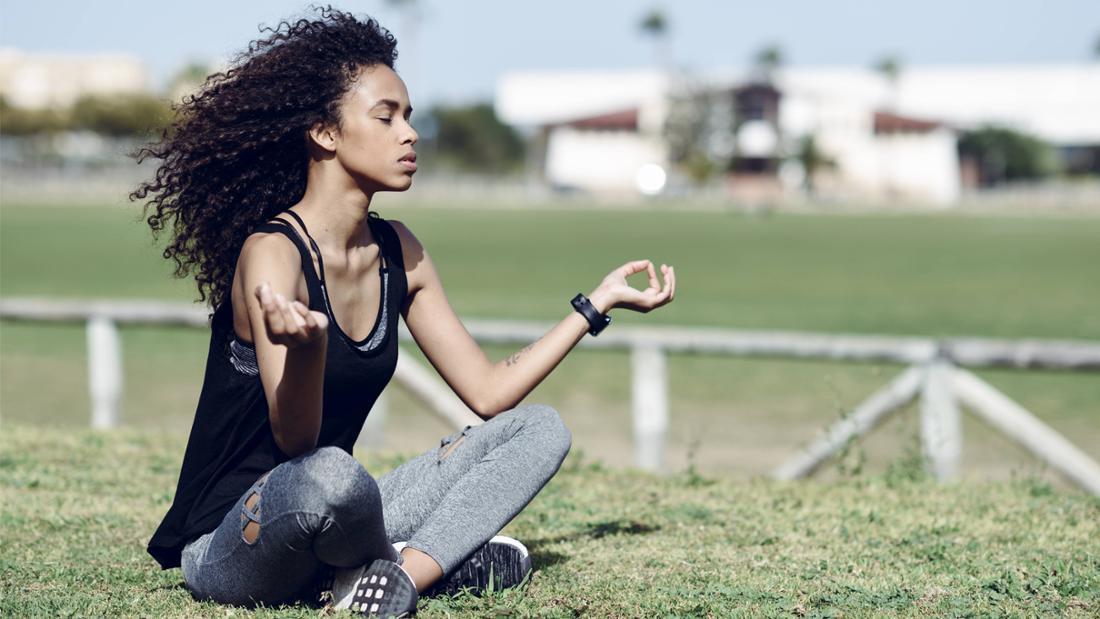 Eine junge Frau in sportlichen Klamotten, die auf dem Gras sitzt und meditiert. Sie hat die Augen zu und hält die Arme hoch und die Fingerspitzen von ihrem Zeigefinger und Daumen zusammen. Neben ihr ist ein Zaun, der eine grüne Fläche absperrt und im Hintergrund ist ein Gebäude zu sehen.