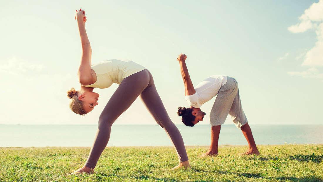 Eine Frau und ein Mann, die sich beide in Sportklamotten herunter strecken. Sie stehen auf einer grünen Grasfläche und im Hintergrund ist das Meer zu sehen.