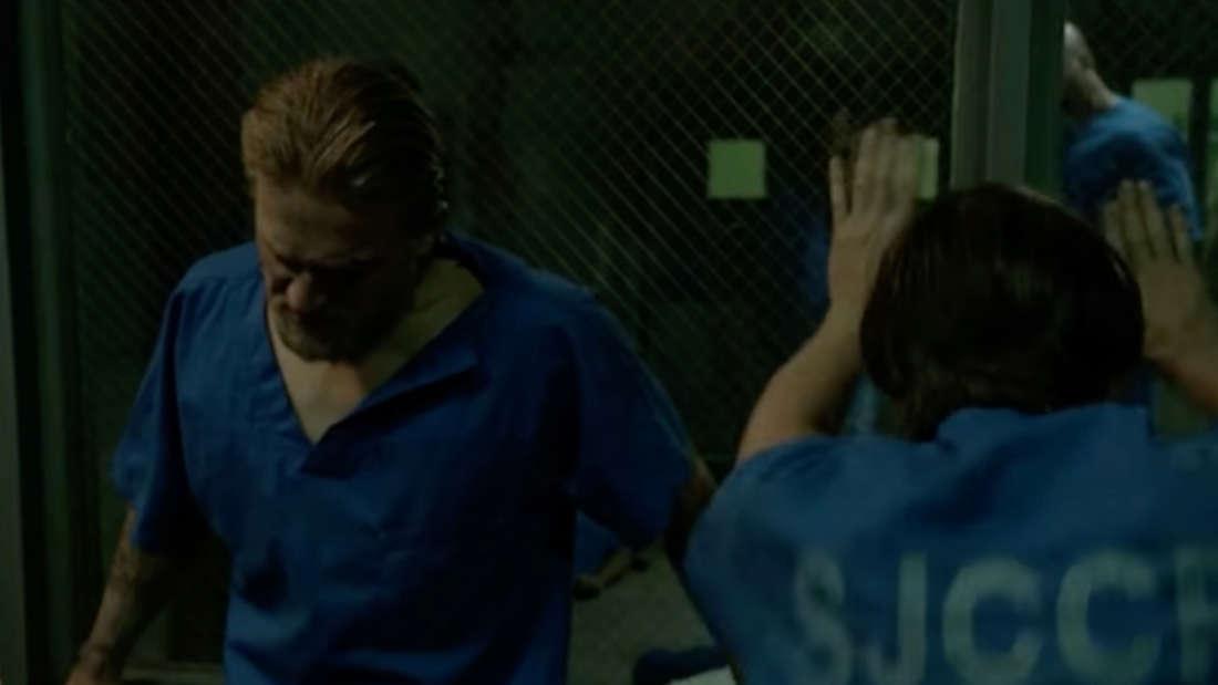 Jax lehnt mit dem Rücken gegen eine Scheibe im Gefängnis. Im Raum hinter ihm wurde gerade Opie ermordet.