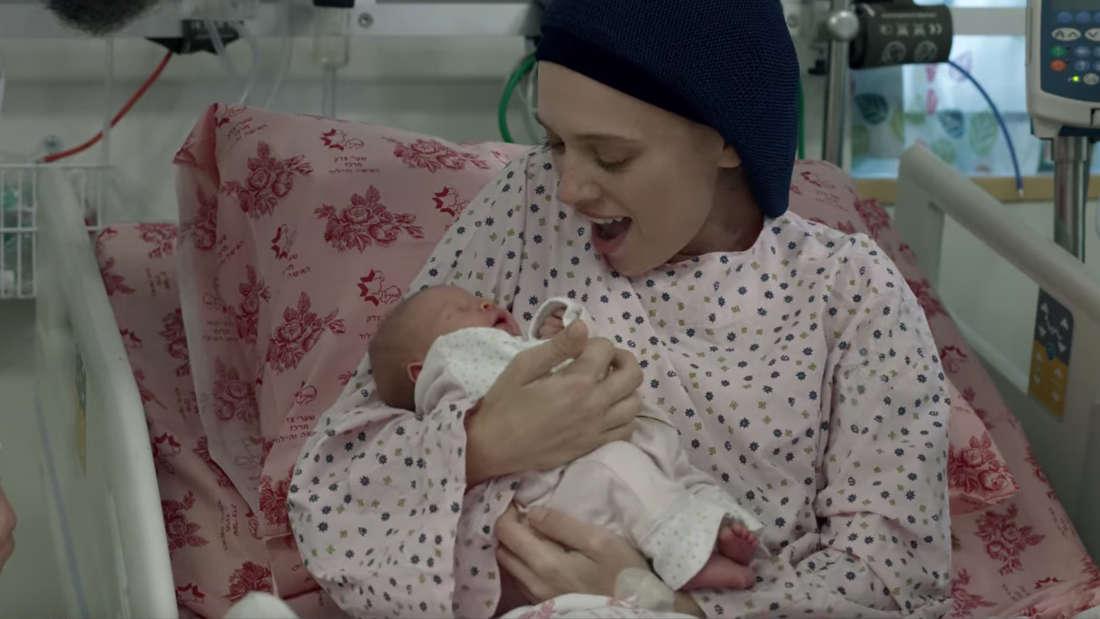 Ruchami hält ihre neugeborene Tochter im Arm