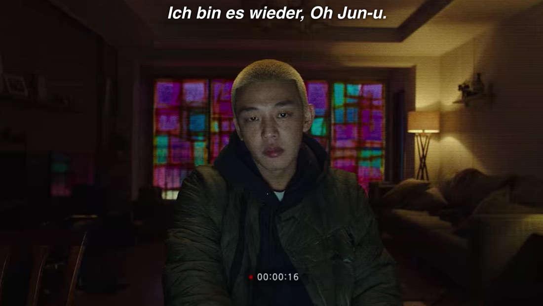Ein junger Mann sitzt in seinem Wohnzimmer und spricht in eine Kamera.